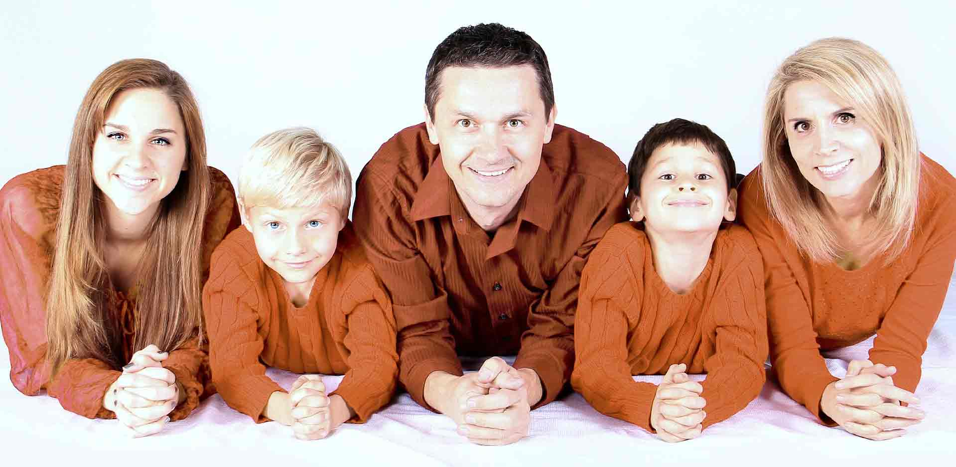 smiling family in orange sweaters lying on their stomachs