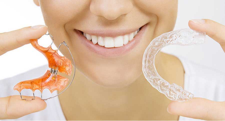 smiling girl holding two types of retainers